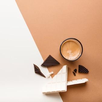 Tavoletta di cioccolato scuro e bianco con bicchiere di caffè su doppio fondale