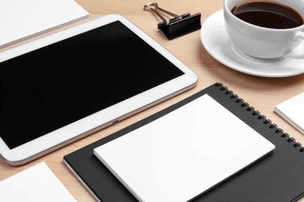 Tavoletta digitale con blocco note, forniture e tazza di caffè sul desktop.