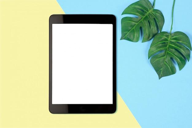 Tavoletta digitale con schermo bianco su sfondo di colore pastello, foto piatta laici