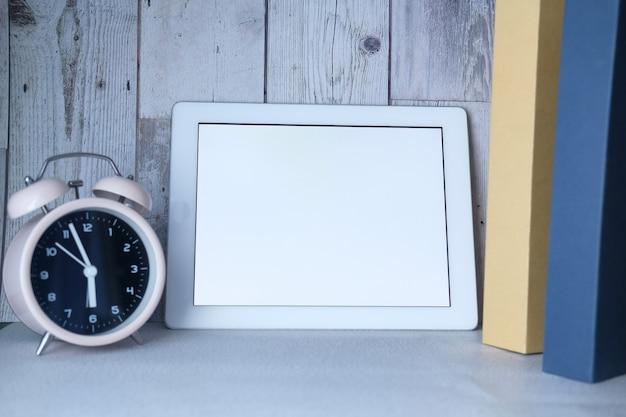 Tavoletta digitale con schermo vuoto, orologio e pila di libri sul tavolo
