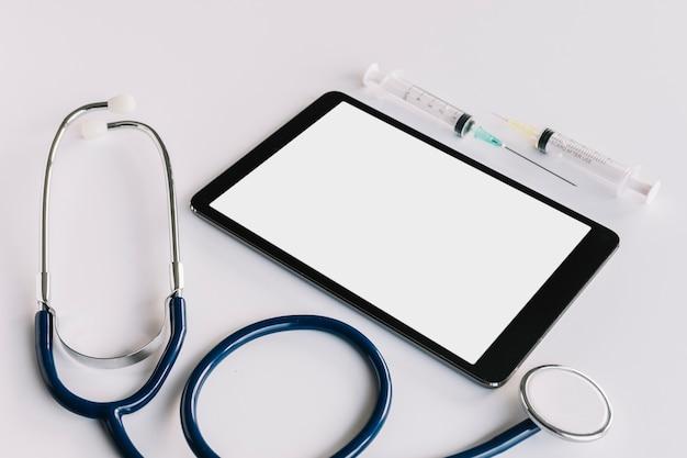 Tavoletta digitale con schermo vuoto; siringa e stetoscopio su sfondo bianco