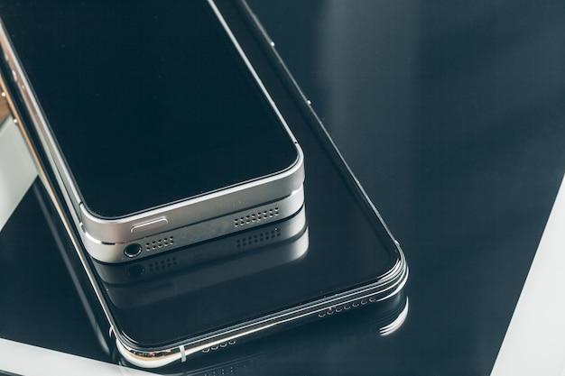 Tavoletta digitale e telefono cellulare, dispositivi elettronici sul tavolo di legno, primi piani,