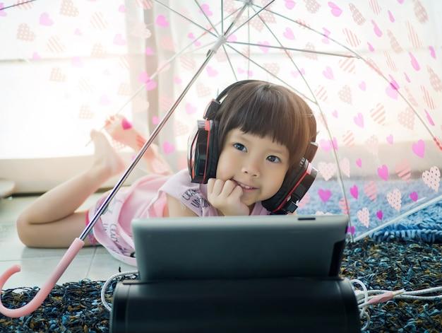 Tavoletta dipendente bambino cinese, ragazza asiatica che gioca smartphone, telefono per bambini, guardare cartoni animati