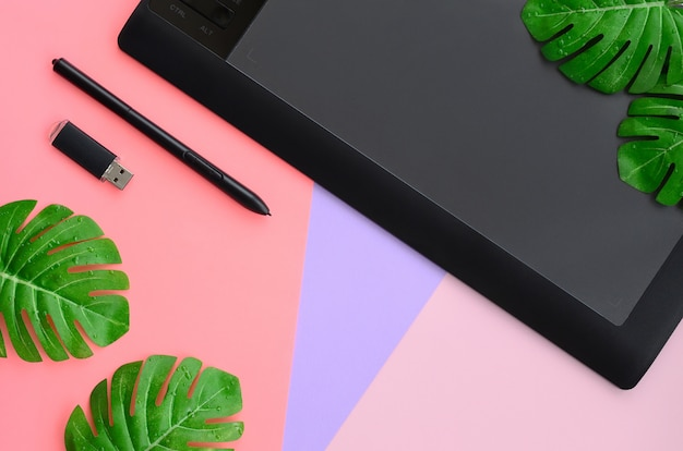 Tavoletta grafica e penna, memory card e foglie di monstera