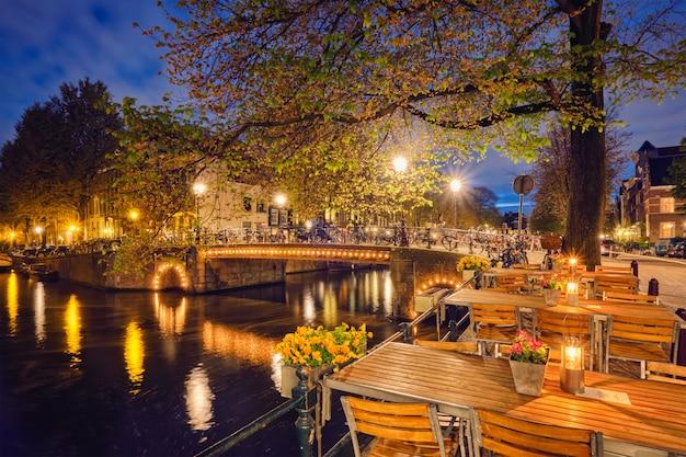 Tavoli di caffè di amsterdam, canale, ponte e case medievali nella e