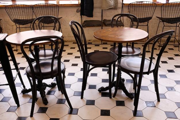 Tavoli e sedie in legno in un bar, ufficio o stanza. design elegante, stile vintage. posto per colazione, incontri di lavoro e trattative aziendali, sala conferenze d'affari.