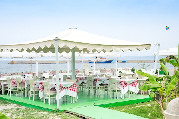 Tavolini del caffè serviti con una tovaglia a colori vicino al mare per vacanze rilassanti