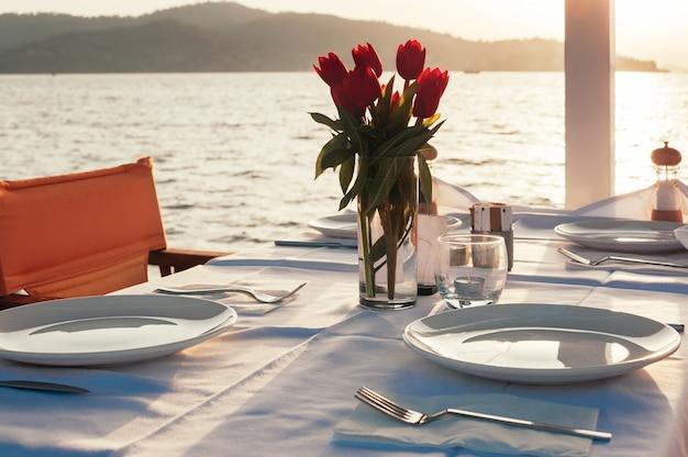 Tavolo apparecchiato con fiori al ristorante sulla spiaggia