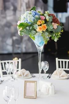 Tavolo apparecchiato per banchetto di nozze con composizione floreale