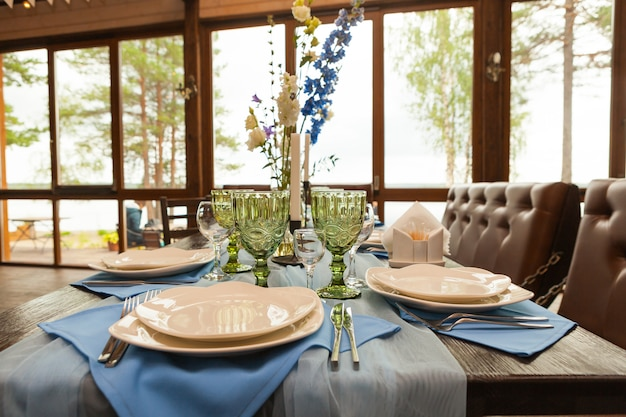 Tavolo apparecchiato per matrimonio con fiori, decorazioni e candele