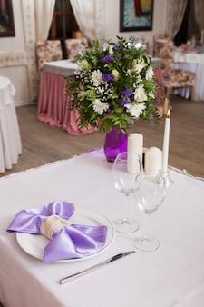 Tavolo apparecchiato per matrimonio, una cena romantica o altri eventi. piatto decorato con un fiocco di stoffa