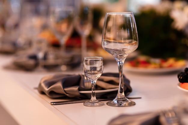 Tavolo apparecchiato per un evento festa o ricevimento di nozze. regolazione della tavola di nozze. bicchieri di vino