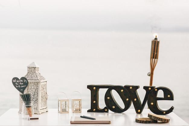 Tavolo bianco con lanterne decorative e lettering in acciaio amore