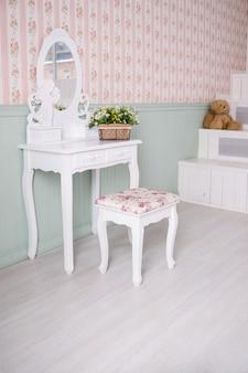 Tavolo boudoir dettagli dell'interno della camera da letto per ragazze e trucchi, acconciature con specchio.