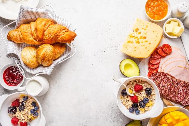 Tavolo colazione continentale con croissant, marmellata, prosciutto, formaggio, burro, muesli e frutta, copia spazio.