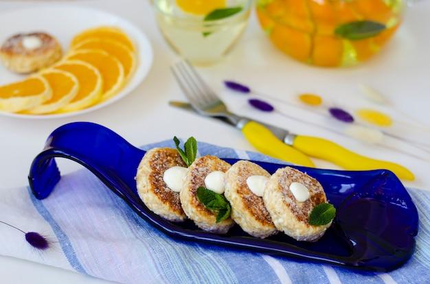 Tavolo colazione sana con cheesecakes di ricotta con teiera di vetro con tè detox. concetto di dieta. cibo a basso contenuto di grassi. senza zucchero. messa a fuoco selettiva