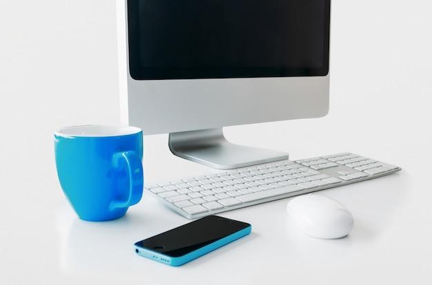 Tavolo computer bianco, tastiera, mouse, tazza blu e telefono.