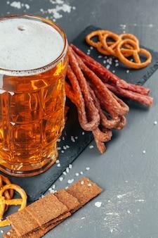Tavolo con boccale di birra e tavola di legno con salsicce