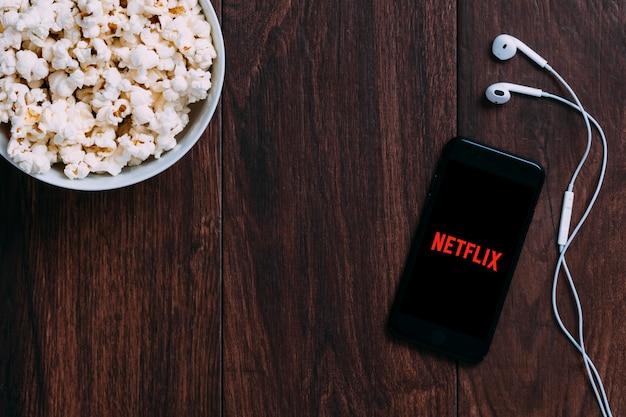 Tavolo con bottiglia di popcorn e logo netflix su apple iphone e auricolare.