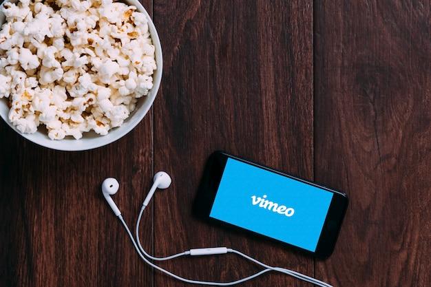 Tavolo con bottiglia di popcorn e logo vimeo su apple iphone e auricolare.