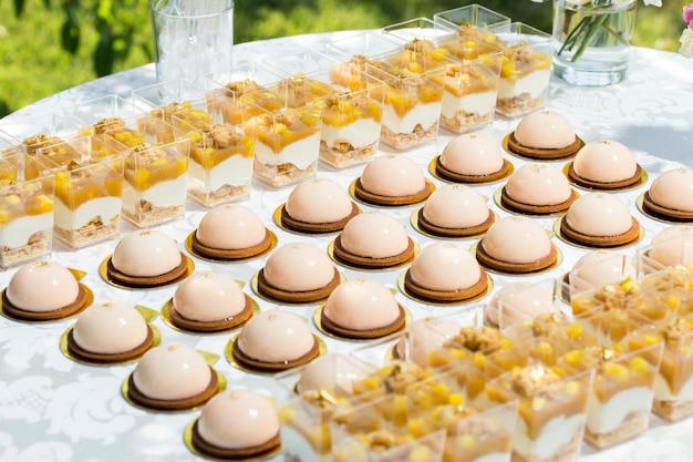 Tavolo con dolci decorati con fiori e torte di amaretti e dessert leggeri in coppa