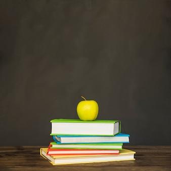Tavolo con pile su libri e mela