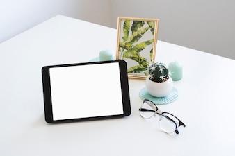 Tavolo con tablet vicino cornice e occhiali da vista