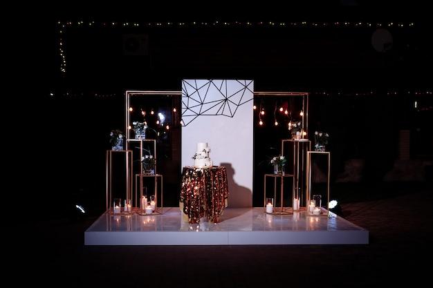 Tavolo con una torta nuziale, candele, luce e fiori. decorazione di nozze