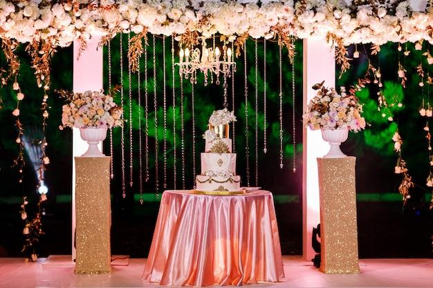 Tavolo con una torta nuziale, candele, luce e fiori.
