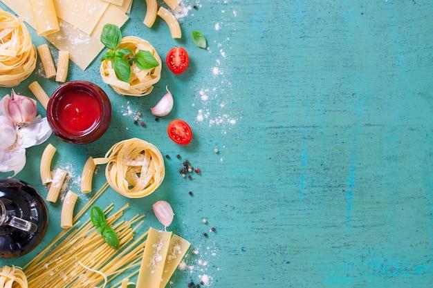 Tavolo con varietà di pasta e salsa di pomodoro