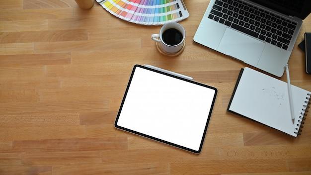 Tavolo creativo vista dall'alto con tablet, computer portatile, guida colori e caffè sulla scrivania in legno.