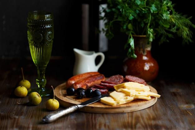 Tavolo da aperitivo snack di carne, salsicce fritte, formaggio, salame, olive e un bicchiere di vino su un tavolo scuro
