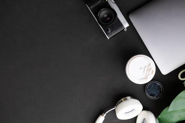 Tavolo da artista computer, macchina fotografica, caffè e cuffie sul nero con vista dall'alto