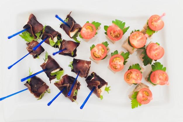 Tavolo da buffet assortimento di tartine. servizio banchetti in ristorante. approvvigionamento alimentare, spuntini sul piatto bianco.