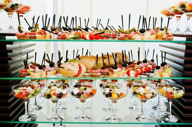 Tavolo da buffet della reception con hamburger, snack freddi, carne e insalate