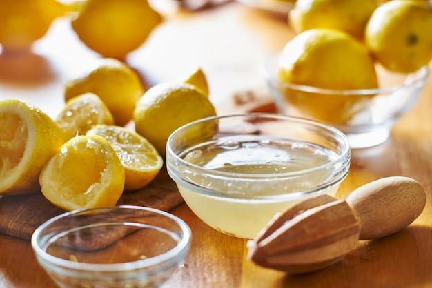 Tavolo da cucina con ciotola piena di succo di limone appena spremuto con alesatore in legno