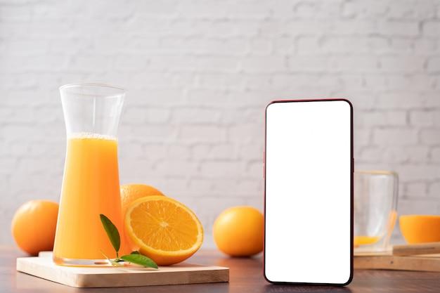 Tavolo da cucina con schermo vuoto smart phone, cellulare, tablet e brocca di succo d'arancia.