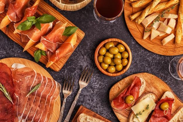 Tavolo da cucina italiano con prosciutto, formaggio, olive.