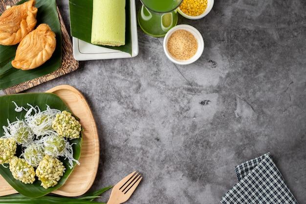 Tavolo da dessert dolce tailandese con soffio di pollo al curry, riso-crespella di fagioli verdi e bicchiere di erbe