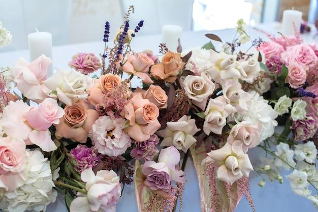 Tavolo da evento bianco da ristorante servito e decorato con delicati fiori freschi