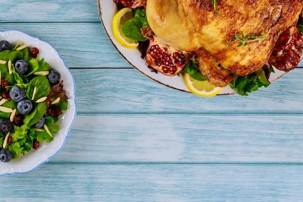 Tavolo da festa con insalata e pollo intero per le vacanze