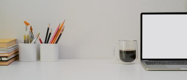 Tavolo da lavoro di design con copia spazio, laptop, cancelleria, strumenti di pittura, libri e tazza di caffè
