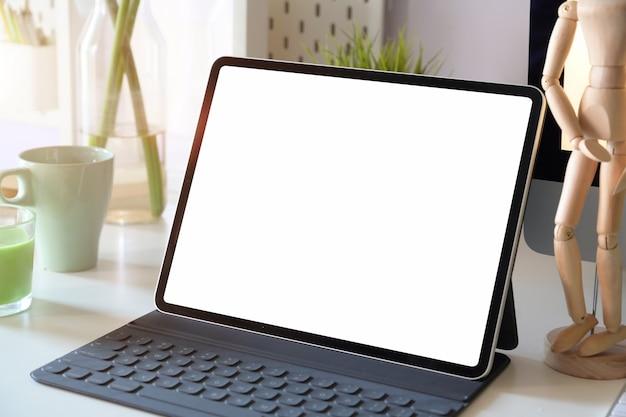 Tavolo da lavoro di ufficio bianco con tablet mockup schermo vuoto