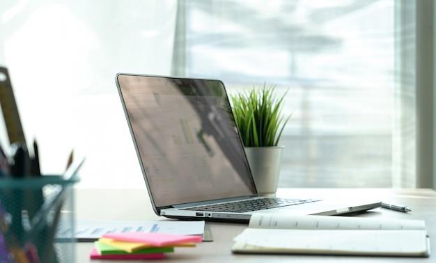 Tavolo da lavoro in ufficio con un computer portatile per lavoro creativo