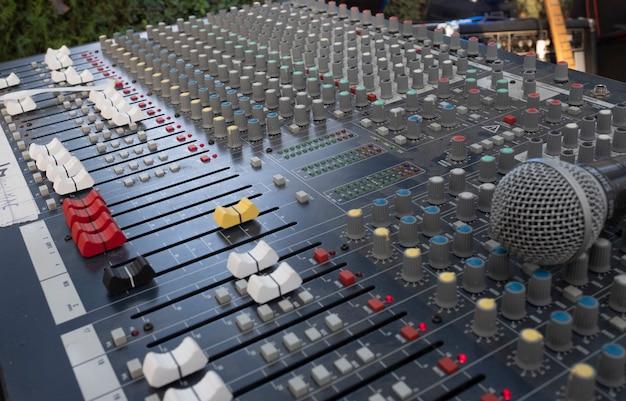 Tavolo da mixaggio sonoro per un concerto con microfono in primo piano