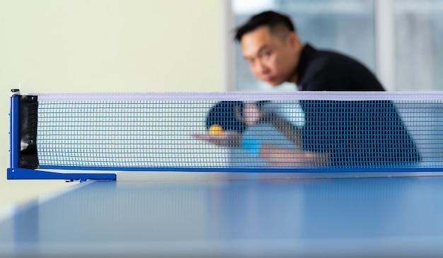 Tavolo da ping pong, tennis da tavolo da gioco maschile con racchetta e palla in un palazzetto dello sport