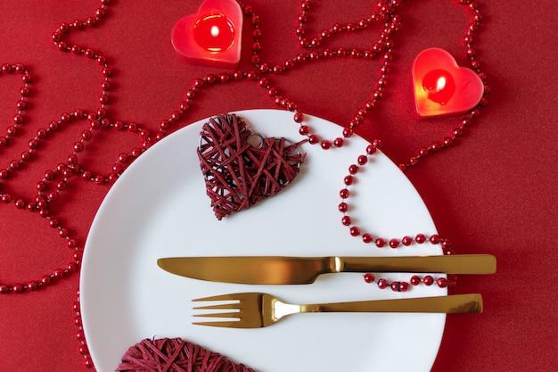 Tavolo da portata con decorazione forchetta, coltello, tovagliolo e cuore per san valentino. cena di san valentino.