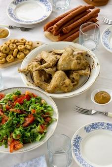 Tavolo da pranzo con ali di pollo fritto, insalata di pomodori e snack