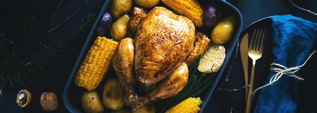 Tavolo da pranzo di natale con pollo su oscurità
