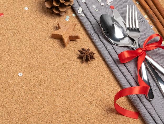 Tavolo da pranzo di natale con posate, tovagliolo grigio e spezie invernali vista dall'alto.